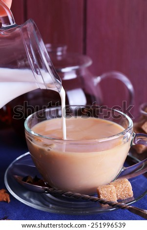 Pouring milk on tea and lump sugar and spices on color wooden planks background