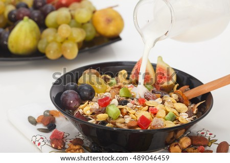 Pouring milk or yogurt into muesli mix cereals, dried fruits, berries in bowl