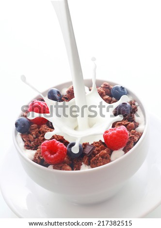 Pouring milk with a splash into a bowl of crunchy breakfast cereal topped with fresh berries with raspberries and blueberries over white with copyspace - stock photo