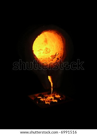 pouring molten metal from a ladle in a foundry - stock photo