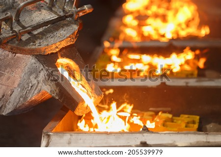 pouring molten metal to casting mold - stock photo