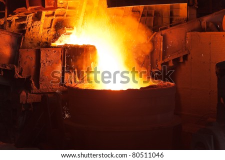 Pouring of liquid metal in open hearth workshop of the metallurgical plant - stock photo