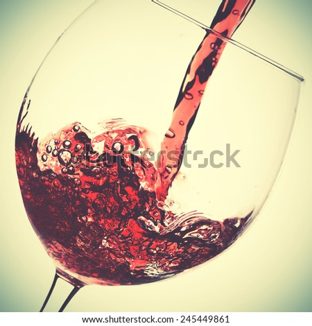 Pouring of red wine in glass. Instagram style filtred image - stock photo