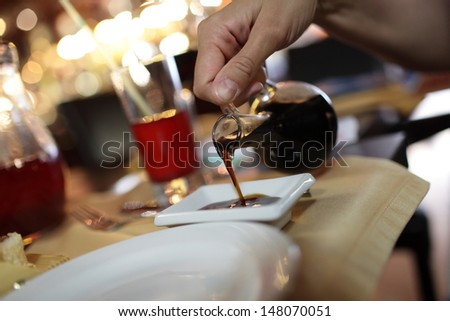 Pouring of soy sauce in the restaurant - stock photo