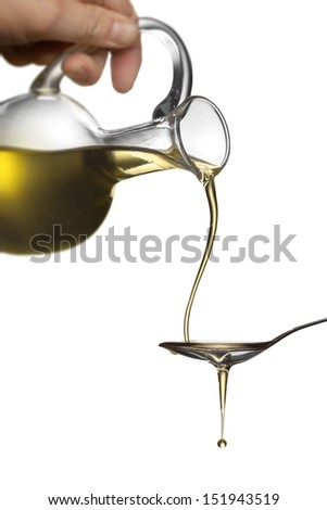 Pouring oil from jar on spoon isolated on white - stock photo