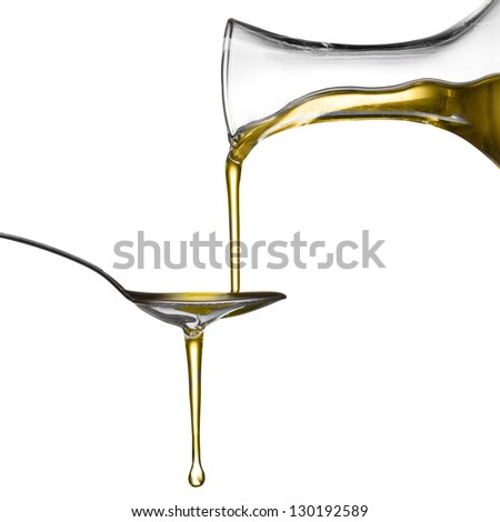 Pouring oil on spoon isolated on white - stock photo