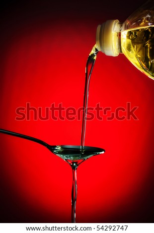 pouring oil on spoon, red background - stock photo