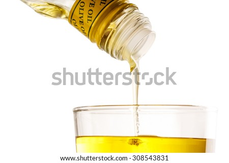 Pouring olive oil from bottle into glass - stock photo