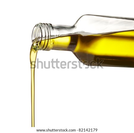 pouring olive oil from glass bottle against white background - stock photo