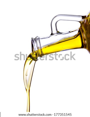 Pouring olive oil from glass bottle, isolated white background - stock photo