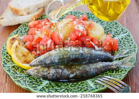 pouring olive oil in very fresh sardines cooked in sea salt - traditional food from Portugal - stock photo