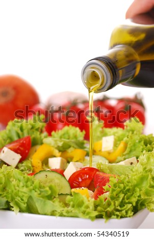 Pouring olive oil on a fresh salad - stock photo