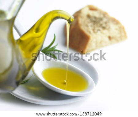 pouring olive oil on a spoon and a slice of bread with oregano - stock photo