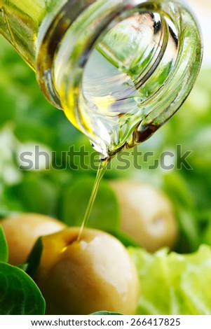 Pouring olive oil on corn salad with olives - stock photo
