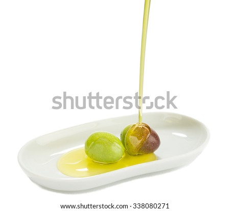 Pouring olive oil on green olives on porcelain dish isolated on white background.  - stock photo