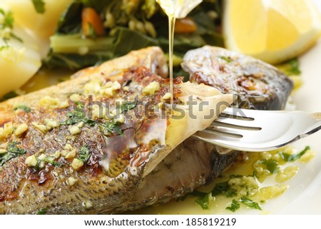 pouring olive oil on very fresh seabream fish grilled - traditional food from Portugal - stock photo