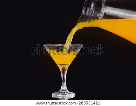 pouring orange juice into glass, Fresh pouring orange juice with fruits  on black background