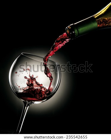 Pouring red wine from a bottle into a glass - stock photo