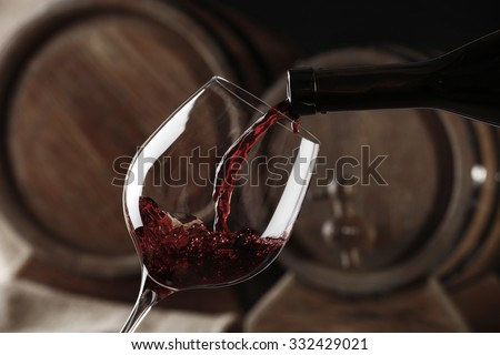 Pouring red wine from bottle into glass,  black and white retro stylization - stock photo