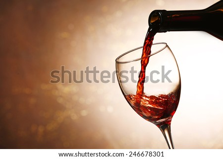 Pouring red wine from bottle into glass on color background - stock photo