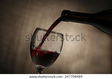 Pouring red wine from bottle into glass on dark background