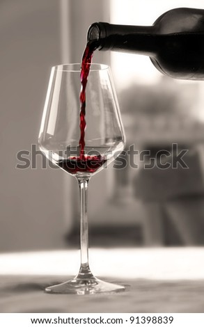 pouring red wine from bottle into wineglass in black and white - stock photo