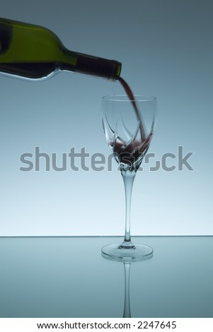 Pouring red wine in a crystal wine glass