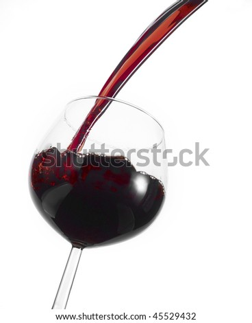 Pouring red wine in a glass, isolated on white.