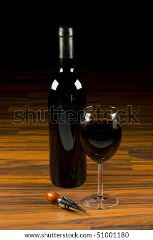 Pouring red wine in glass goblet and accesories in wood background