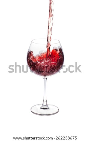 pouring red wine in to wine glass. - stock photo