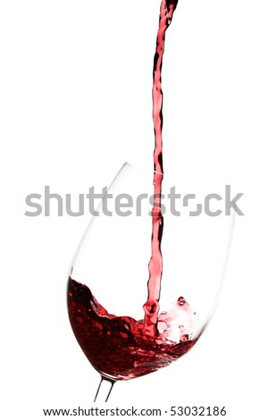 Pouring red wine into a crystal wine glass - stock photo