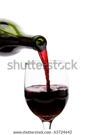 Pouring red wine into a glass - stock photo