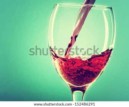 Pouring red wine into a glass on a green background - stock photo