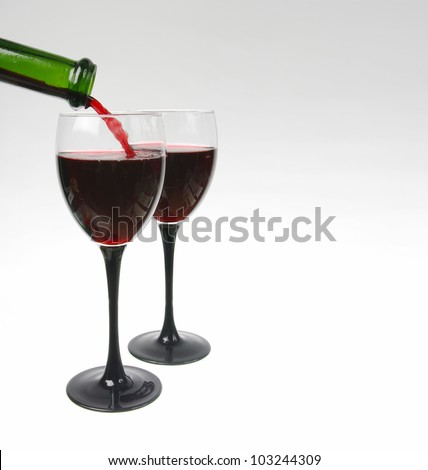 Pouring red wine into a glass. Space for text