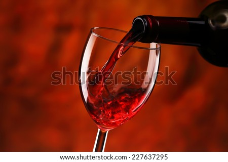 Pouring red wine into glass - stock photo