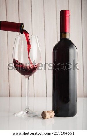 Pouring red wine into glass and bottle on wood background - stock photo