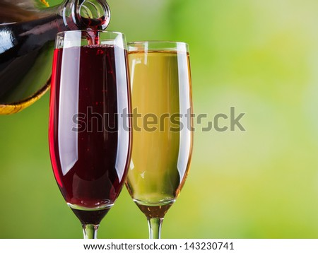 Pouring red wine into glass background - stock photo