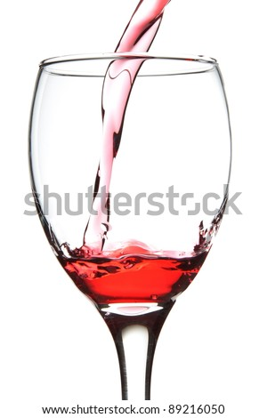 pouring red wine into the glass. - stock photo