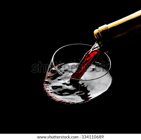 Pouring red wine into the glass against black background