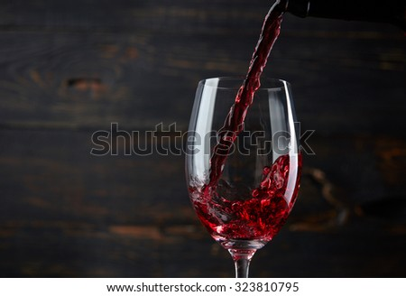 Pouring red wine into the glass against dark wooden background - stock photo