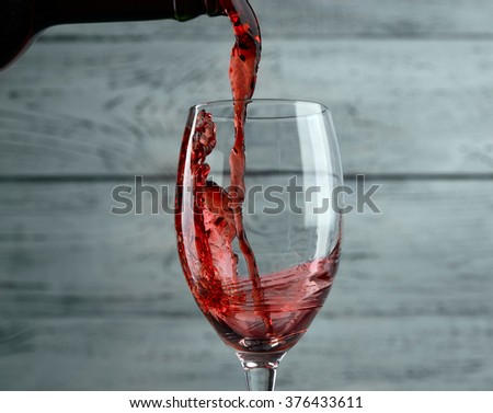 Pouring red wine into the glass against grey wooden background - stock photo