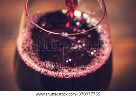 Pouring red wine into the glass against wooden background. Soft focus - stock photo