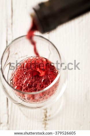 Pouring red wine into the glass crystal white wooden table - stock photo