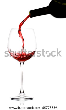 pouring red wine into wine glass on reflective surface - stock photo