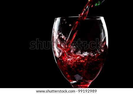 pouring red wine isolated on a black background - stock photo