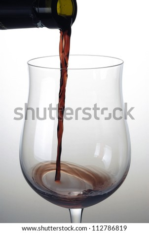 Pouring red wine on a cup