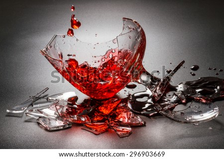 Pouring red wine on broken glass. - stock photo