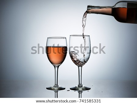 Pouring rose' wine form a bottle into wine glasses.