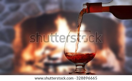 Pouring rred wine in front of fireplace - stock photo