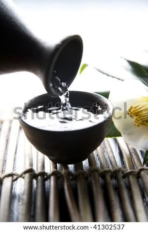 Pouring sake into Japanese traditional cup and white camellia - stock photo